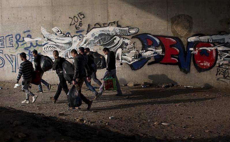 """Un grup de imigranţi părăsesc tabăra """"Jungla"""" din oraşul francez Calais, 23 octombrie 2016."""